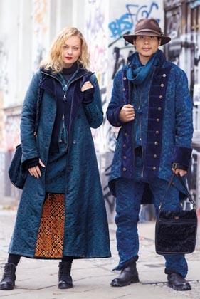 Mann und Frau in auffälligem blauen Brokat Chenille Mänteln mit passender schwarzer brokat Tasche