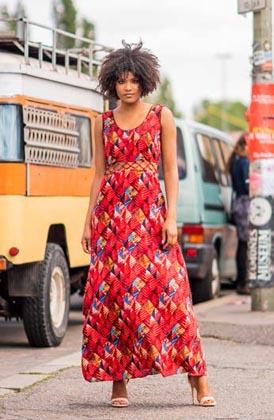 Frau mit leichtem roten Kleid aus ECOVERO vor einem Jeep in Berlin