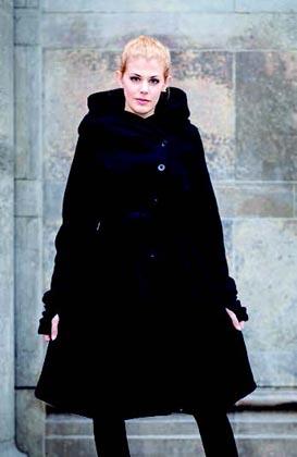 schwarzer Mantel aus Merinowolle vor Steinwand