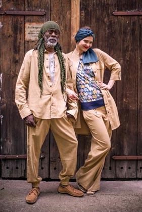 Mann und Frau in Beigen Organic Slap Cotton Jacke und Hose vor Holztor